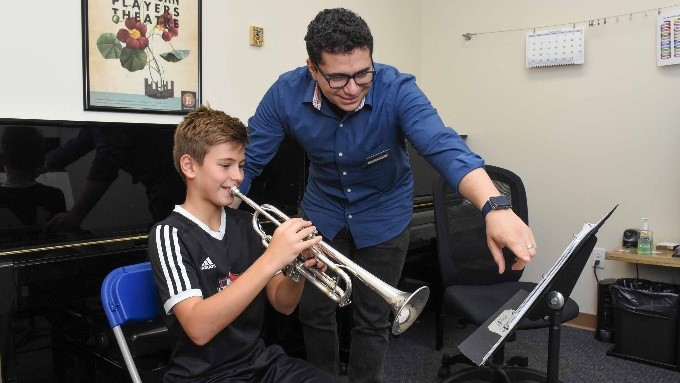 teaher helping student play trumpet